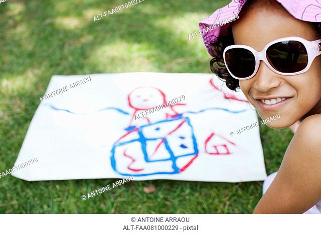 Girl with drawing on grass