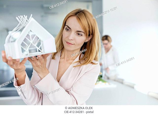 Female architect examining model in office