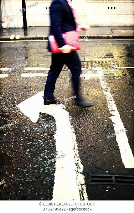 Unrecognizable businessman with portfolio walking down in the street with a turn arrow painted on the asphalt in the city of London, England, UK