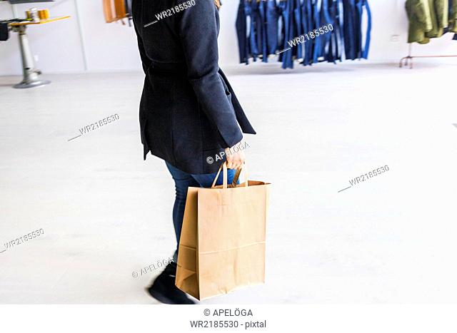 Low section of woman carrying shopping bag in factory