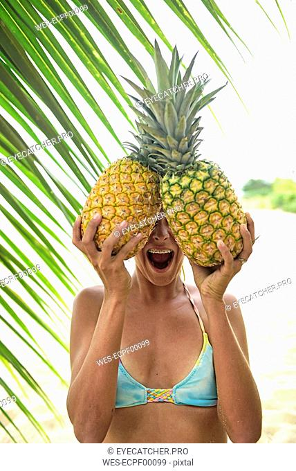 Young woman holding two pineapples at palm tree