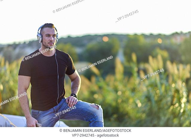 thoughtful young man listening to music with headphones while standing in nature in evening sun. Half Greek and half English ethnicity