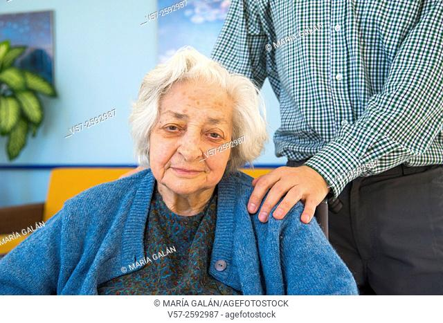 Portrait of old woman in a nursing home and a man putting his hand on her shoulder