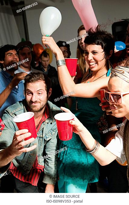 People dancing at party with plastic cups