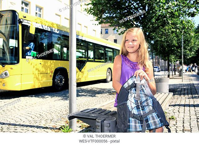Girl with backpack sitting at bus station