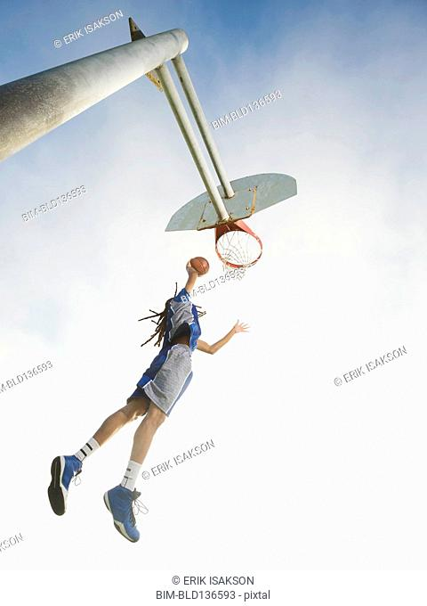 Black basketball player dunking ball in hoop