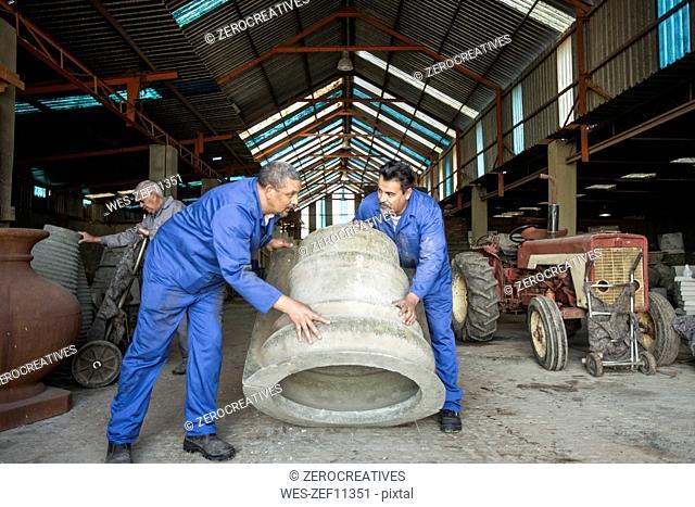 Men working in industrial pot factory