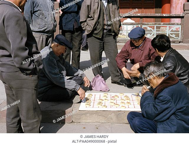 China, Xinjiang Province, Urumqi, group of people playing mah-jong on ground