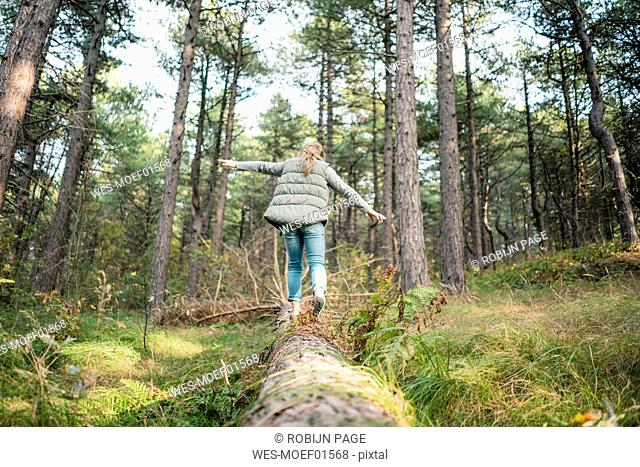 Little girl balancing on a tree trunk in the forest