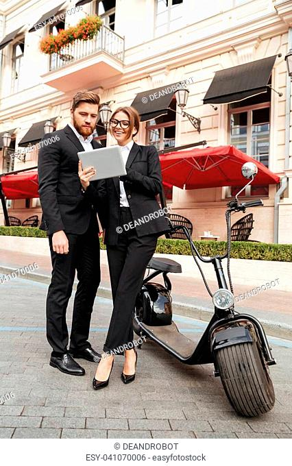 Full length portrait of a smiling attractive couple in smart clothes standing and using tablet computer on a city street near motorbike