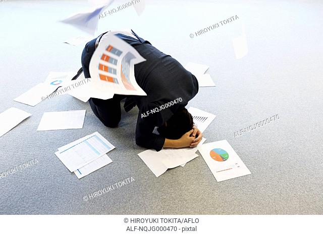 Young Japanese businessman with lots of scattered documents