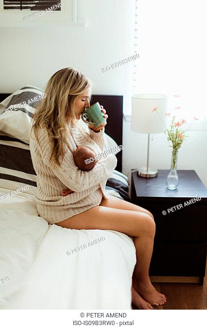 Mid adult woman sitting on bed drinking coffee whilst cradling new born baby daughter