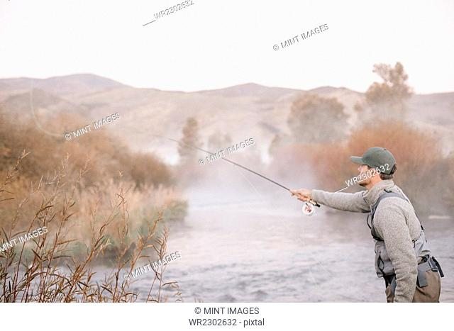 A man standing casting his fishing rod, fly fishing from a riverbank