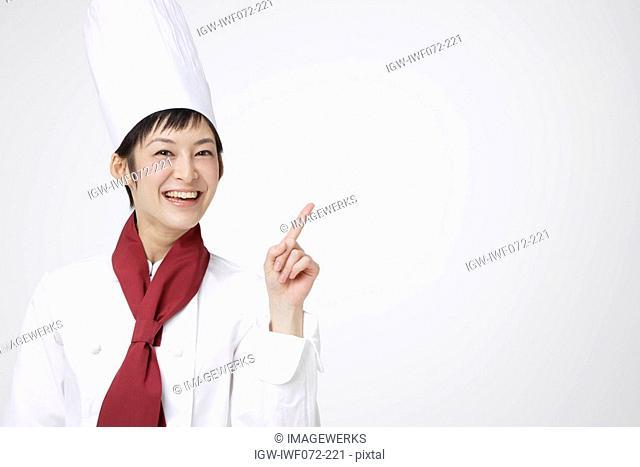 Female chef showing finger, smiling, portrait, close-up