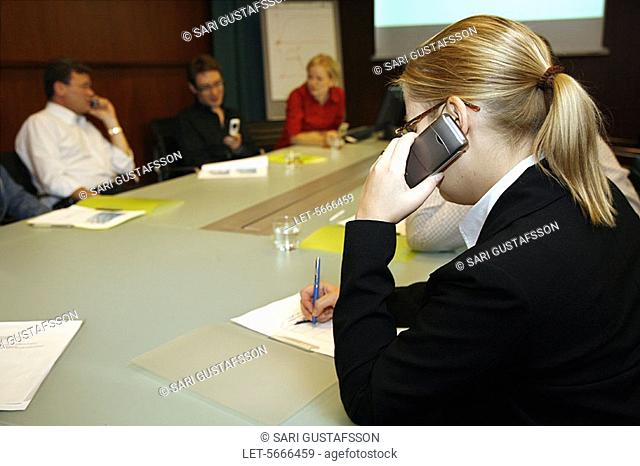 Woman using cell phone at meeting