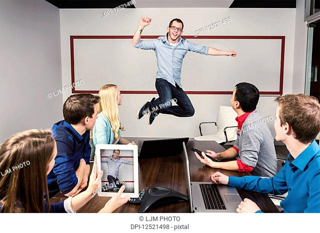 Young millennial business professional jumping to celebrate an accomplishment with his co-workers working in a conference room during a presentation and one of...