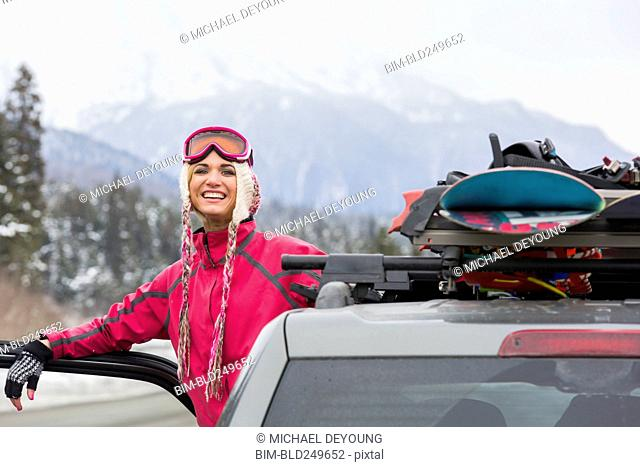Caucasian woman posing at car with snowboards