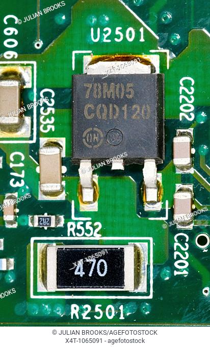 close up photograph of electronic components on a computer mother board showing a voltage regulator chip