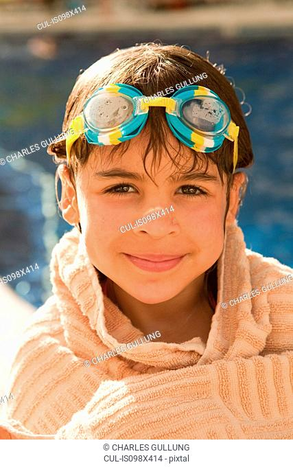 Portrait of young girl with swimming goggles, wrapped in a towel