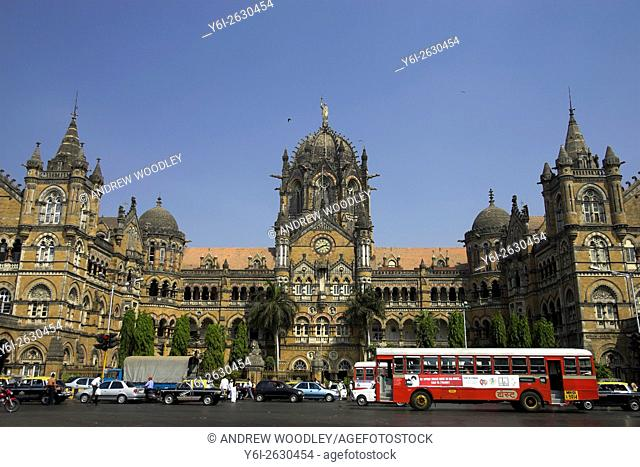 Red single decker bus passes Victoria Terminus municipal railway station Mumbai Bombay