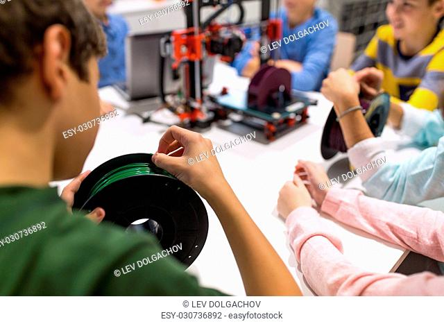 education, children, technology, science and people concept - group of kids with 3d printer and filament spool at robotics school lesson