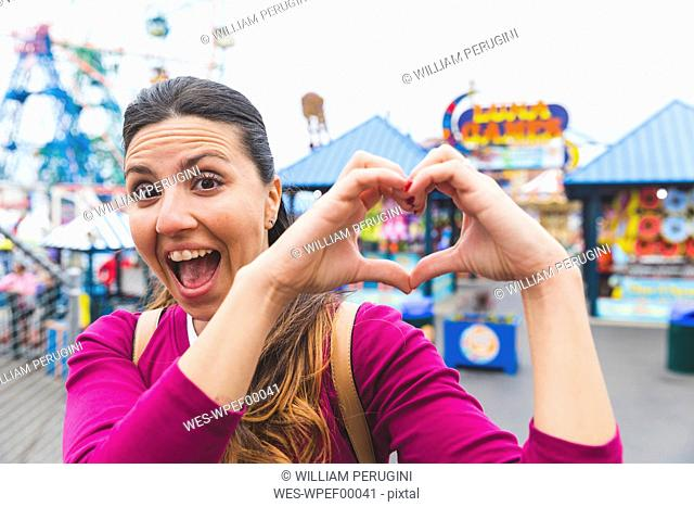 USA, New York, portrait of excited woman at Coney Island shaping heart with her hands