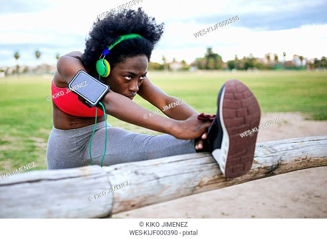 ng black athlete listening music with headphones while warming up