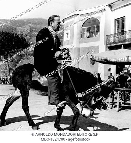 Humphrey Bogart riding on a donkey during the filming Beat the Devil. The actor Humphrey Bogart riding a donkey to Amalfi; the actor is in Italy for some takes...