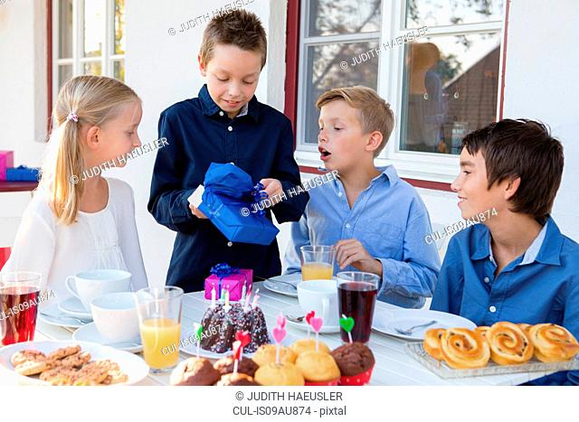 Boy with siblings unwrapping birthday gifts on patio