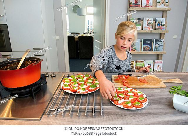 Kaatsheuvel, Netherlands. Young blonde schoolgirl preparing a sidedish to go with Lasagna dish dinner