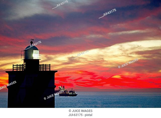 Scenic view of lighthouse and ship at sunset