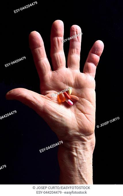 hand and pills senior woman