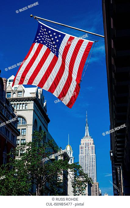 View of American flag and the Empire State Building from fifth avenue, New York, USA