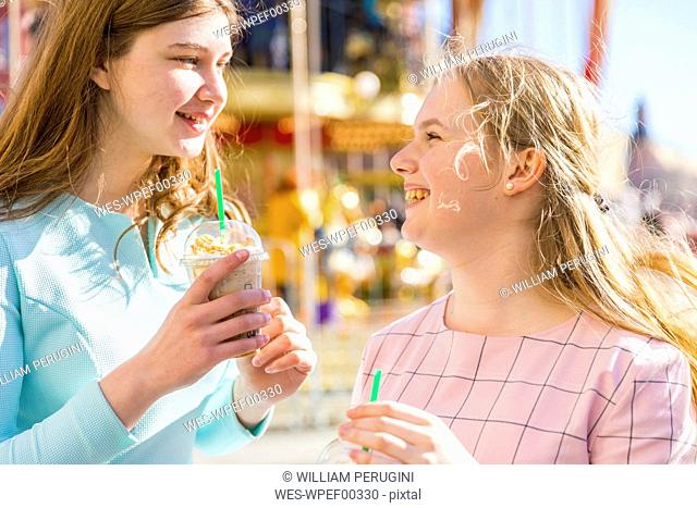 Russia, Moscow, teenage girls drinking a delicious frappe at funfair