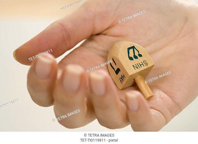 Hand holding Jewish Dradle