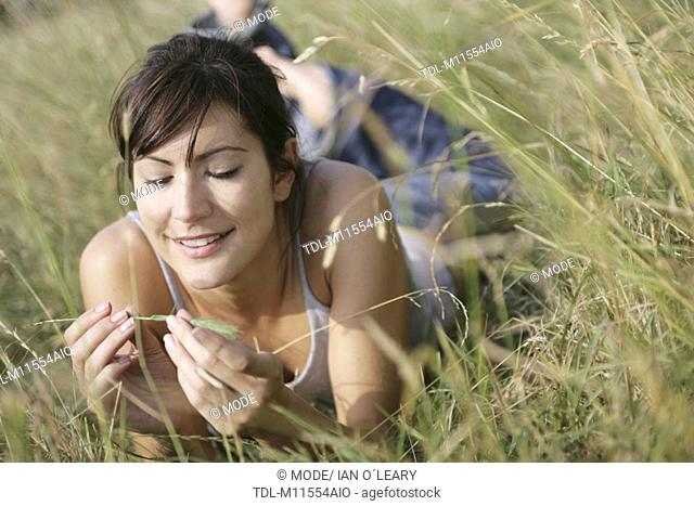 A girl lying in a field playing with a blade of grass