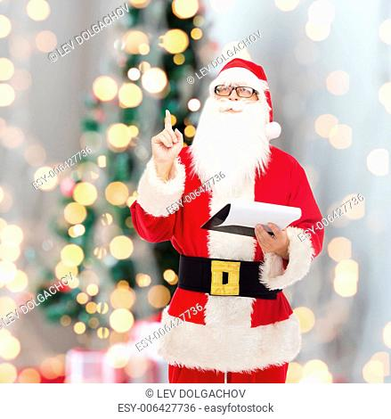 christmas, holidays, gesture and people concept - man in costume of santa claus with notepad pointing finger up over tee lights background