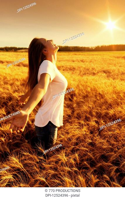 A woman stands in a wheat field with arms outstretched in surrender; Alberta, Canada