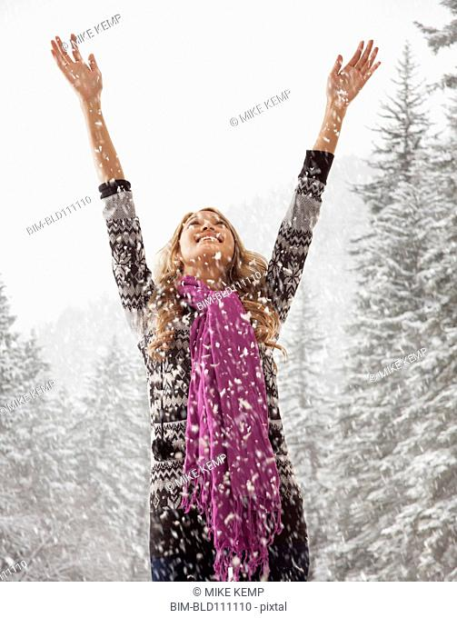 Mixed race woman playing in snow