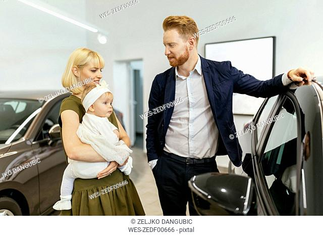 Family in car dealership choosing family vehicle