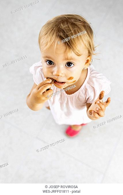 Portrait of little girl eating chocolate cookie