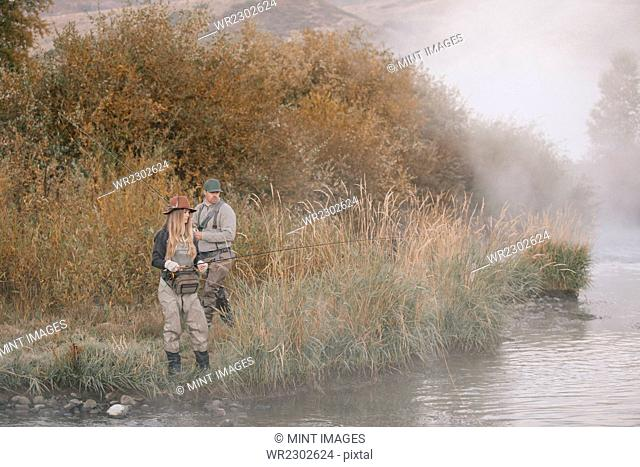 A man and woman standing on a riverbank, fishing