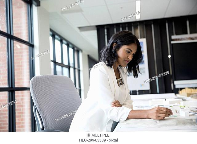 Female architect reviewing model at table in office