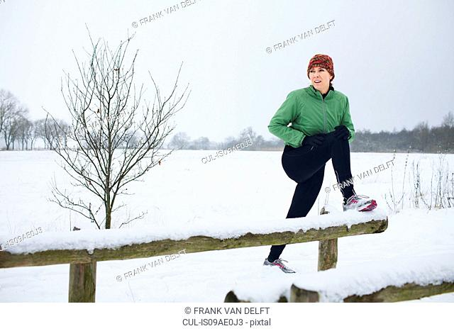 Female jogger stretching before run in snow covered scene