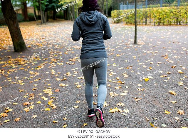 fitness, sport, people, wear and healthy lifestyle concept - close up of young woman running in autumn park