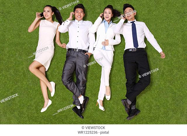 Young people lying on grass talking on the phone