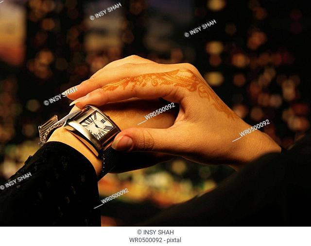Arab lady with henna on hands looking at watch