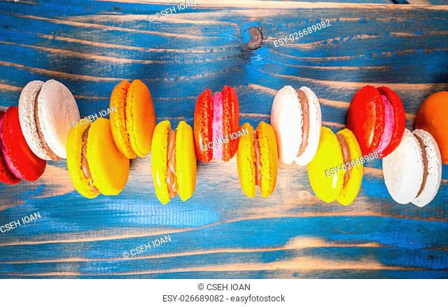 Top view of colorful macarons on blue wooden background