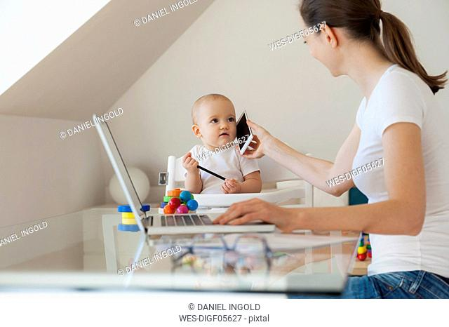 Mother working with little daughter playing at table at home