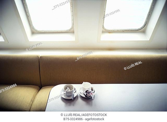 Two empty coffee cups on the dining table of a boat. Mediterranean Sea, Spain, Europe